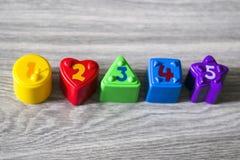 Красочные пластичные формы с номерами на деревянной предпосылке Стоковые Фотографии RF