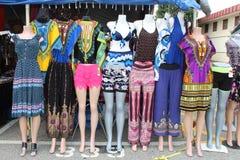 Красочные платья и брюки на манекенах на внешнем блошинном стоковая фотография