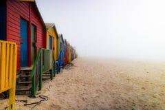 Красочные раздевалки на пляже Muizenberg в тумане стоковое фото rf