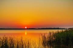 Красочные расшивы солнца над озером Стоковое Изображение