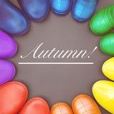 Красочные резиновые ботинки всех цветов радуги стоят на серой поверхности внутри стоковое изображение rf