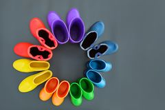 Красочные резиновые ботинки всех цветов радуг-красной, оранжевой, желтой, зеленой, голубой, cyan и фиолетовой стойки на серой пов стоковая фотография