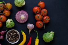 Красочные специи в ложках и томатах на темной винтажной предпосылке Взгляд сверху Ингридиенты еды и кухни Vegan или диета Стоковое фото RF