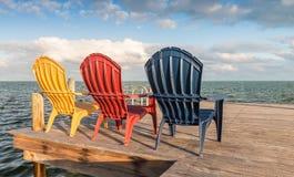 Красочные стулья, который подвергли действию для захода солнца осматривают как увидено от задней части Стоковая Фотография