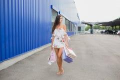 Красочные сумки летая: розовый, желтый, белый в руках счастливой и усмехаясь девушки с коричневыми волосами, ходя по магазинам ко Стоковая Фотография RF