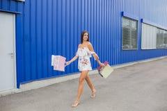 Красочные сумки летая: розовый, желтый, белый в руках счастливой и усмехаясь девушки с коричневыми волосами, ходя по магазинам ко Стоковая Фотография
