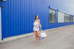 Красочные сумки летая: розовый, желтый, белый в руках счастливой и усмехаясь девушки с коричневыми волосами, ходя по магазинам ко Стоковое Изображение RF