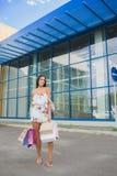 Красочные сумки: розовый, желтый, белый в руках счастливой и усмехаясь девушки с коричневыми волосами, ходя по магазинам концепци Стоковая Фотография