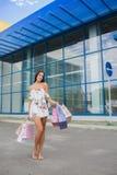 Красочные сумки: розовый, желтый, белый в руках счастливой и усмехаясь девушки с коричневыми волосами, ходя по магазинам концепци Стоковые Изображения
