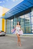 Красочные сумки: розовый, желтый, белый в руках счастливой и усмехаясь девушки с коричневыми волосами, ходя по магазинам концепци Стоковое Изображение RF