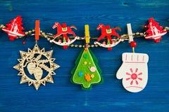 Красочные украшения рождества и света рождества на веревочке на голубой деревянной предпосылке Стоковое Изображение RF