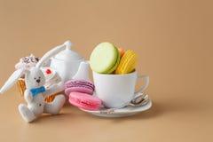Красочные французские macaroons и чашка чаю на бежевой предпосылке Стоковое Изображение