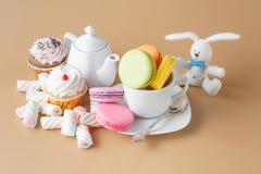 Красочные французские macaroons и чашка чаю на бежевой предпосылке Стоковая Фотография RF