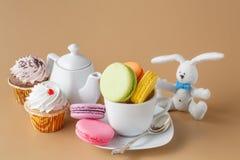 Красочные французские macaroons и чашка чаю на бежевой предпосылке Стоковые Изображения