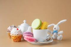 Красочные французские macaroons и чашка чаю на бежевой предпосылке Стоковые Изображения RF