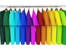 Красочные футболки при вешалки изолированные на белизне Стоковая Фотография
