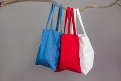 Красочные хозяйственные сумки вися на ветви дерева Стоковые Изображения