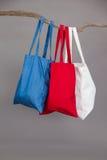 Красочные хозяйственные сумки вися на ветви дерева Стоковая Фотография