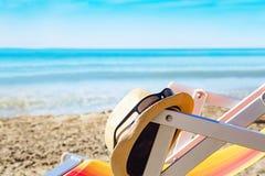 Красочные шезлонги и шляпа солнца на пляже Стоковая Фотография RF
