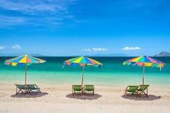 Красочные шезлонги с зонтиками на солнечный день стоковые изображения