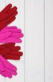 Красочные шерстяные перчатки на женщина, одежда на осень или зима, космос экземпляра для текста на белых досках Стоковые Изображения