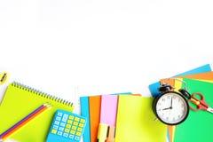 Красочные школьные принадлежности, книга, и будильник на белизне Взгляд сверху, плоское положение Взгляд сверху, космос экземпляр Стоковые Изображения