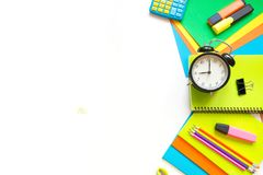 Красочные школьные принадлежности, книга, и будильник на белизне Взгляд сверху, плоское положение Взгляд сверху, космос экземпляр Стоковая Фотография