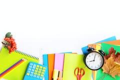 Красочные школьные принадлежности, книга, и будильник на белизне Взгляд сверху, плоское положение Взгляд сверху, космос экземпляр Стоковое фото RF