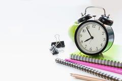 Красочные школьные принадлежности, книга и будильник на белизне конец вверх задняя школа к Стоковые Изображения