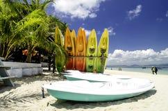 Красочные штабелированные каяки на тропическом пляже с пасмурной синью s Стоковое Фото
