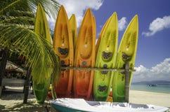 Красочные яркие каяки на белом песочном seashore с пасмурной предпосылкой голубого неба Стоковая Фотография