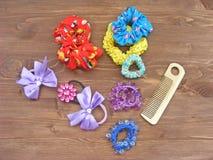 Красочные, яркие hairpins детей с щеткой для волос на деревянной предпосылке Стоковые Изображения