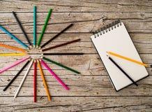 Красочные crayons и тетрадь карандаша на деревянной предпосылке Стоковая Фотография RF