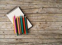 Красочные crayons и тетрадь карандаша на деревянной предпосылке Стоковые Фотографии RF