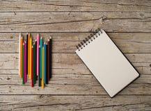 Красочные crayons и тетрадь карандаша на деревянной предпосылке Стоковая Фотография