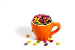 Красочные dragees в оранжевой чашке Стоковые Фото