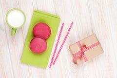 Красочные macarons, чашка молока и подарочная коробка Стоковые Изображения RF