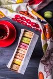 Красочные macaroons в чае подарочной коробки и плодоовощ на деревянной предпосылке Взгляд сверху Стоковое Изображение