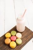 Красочные macaroons и бутылка молока на винтажной разделочной доске Стоковые Изображения RF