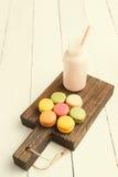 Красочные macaroons и бутылка молока на винтажной разделочной доске Стоковые Фото