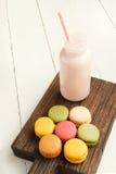 Красочные macaroons и бутылка молока на винтажной разделочной доске Стоковые Изображения
