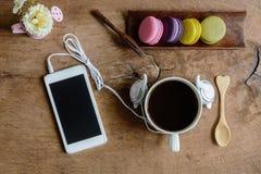 Красочные macaroons и чашка кофе с мобильным телефоном Стоковая Фотография
