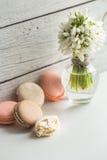 Красочные macaroons с цветками на красивой деревянной предпосылке стоковая фотография rf