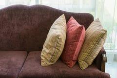 Красочные striped подушки на красной софе в роскошной живущей комнате Стоковое Фото