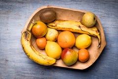 Красочный ассортимент плодоовощ в деревянном шаре изолированном на голубом деревянном столе Стоковая Фотография RF