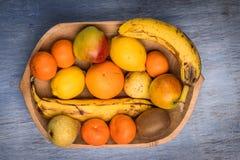 Красочный ассортимент плодоовощ в деревянном шаре изолированном на голубом деревянном столе Стоковое фото RF
