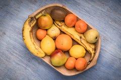 Красочный ассортимент плодоовощ в деревянном шаре изолированном на голубом деревянном столе Стоковые Фотографии RF