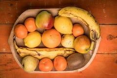 Красочный ассортимент плодоовощ в деревянном шаре изолированном на оранжевом деревянном столе Стоковые Изображения RF