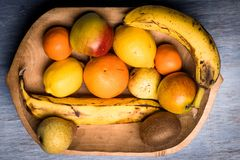 Красочный ассортимент плодоовощ в деревянном шаре на голубом деревянном столе Стоковые Фото