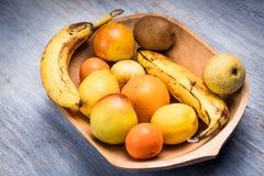 Красочный ассортимент плодоовощ в деревянном шаре на голубом деревянном столе Стоковые Изображения